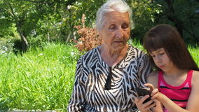 Famille avec le téléphone de téléphone La petite-fille heureuse montre à grand-mère un téléphone portable Famille avec le télépho banque de vidéos
