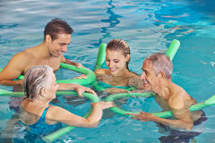 Famille avec les couples supérieurs dans l'eau de la piscine Image stock