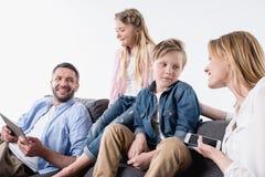 Famille avec les dispositifs numériques se reposant sur le sofa ensemble Photos stock