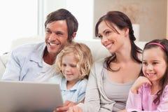 Famille avec plaisir utilisant un carnet Image libre de droits