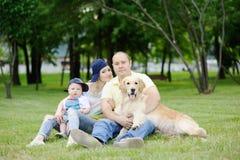 Famille avec un chien d'arrêt de chien sur l'herbe Images stock