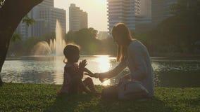 Famille ayant l'amusement au parc avec le lac et les gratte-ciel sur le fond clips vidéos