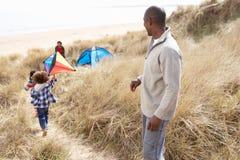 Famille ayant l'amusement avec le cerf-volant en dunes de sable Photos stock