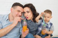 Famille ayant l'amusement buvant du jus d'orange utilisant des pailles Photos libres de droits
