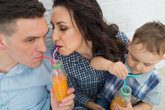 Famille ayant l'amusement buvant du jus d'orange utilisant des pailles Photographie stock
