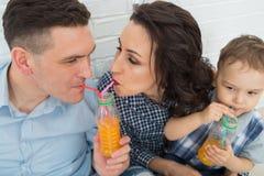 Famille ayant l'amusement buvant du jus d'orange utilisant des pailles Image stock