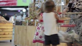 Famille ayant l'amusement dans le centre commercial conduisant un caddie clips vidéos