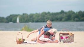 Famille ayant l'amusement de ferroutage des vacances de plage banque de vidéos
