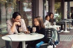 Famille ayant l'amusement en café extérieur Image stock