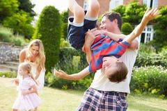 Famille ayant l'amusement jouant dans le jardin Photo stock