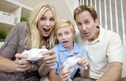 Famille ayant l'amusement jouer le jeu visuel de console Images libres de droits