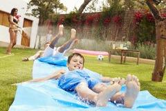 Famille ayant l'amusement sur la glissière d'eau dans le jardin Images libres de droits