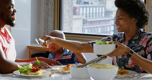 Famille ayant la nourriture à la table de salle à manger dans une maison confortable 4k clips vidéos