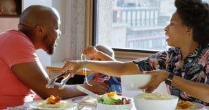 Famille ayant la nourriture à la table de salle à manger dans une maison confortable 4k banque de vidéos