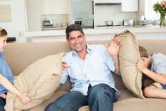 Famille ayant le combat de coussin sur le sofa Photo stock