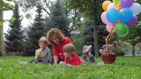 Famille ayant le pique-nique dans le parc d'été, mouvement lent banque de vidéos
