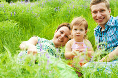 Famille ayant le reste dans l'herbe Photo libre de droits