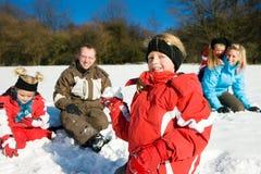 Famille ayant un combat de boule de neige Photos stock