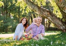 Famille ayant un pique-nique dans le parc Photos libres de droits