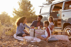 Famille ayant un pique-nique près de leur camping-car, intégral Photos stock