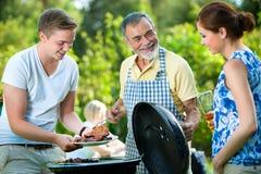 Famille ayant une réception de barbecue Images libres de droits