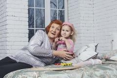 Famille, belle petite petite-fille de bébé et grand-mère dans Noël heureux Photo libre de droits