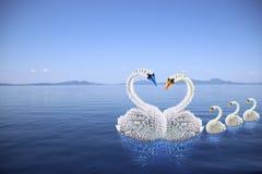 Famille blanche d'origami de cygnes dans l'amour sur la mer Images stock