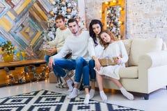 Famille célébrant à la maison père, mère et enfants sur le fond de l'arbre de Noël Nouvelle année et Noël Photographie stock