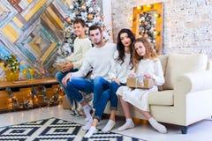 Famille célébrant à la maison père, mère et enfants sur le fond de l'arbre de Noël Nouvelle année et Noël Photo stock