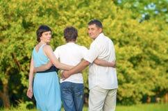 Famille caucasienne du temps trois passant ensemble embrassé en parc d'été Image horizontale Photo stock