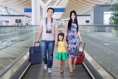 Famille chinoise avec des valises sur l'escalator Photos libres de droits