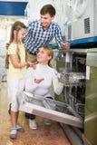 Famille choisissant la machine de vaisselle Photo stock