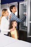 Famille choisissant le réfrigérateur dans le magasin Photos libres de droits