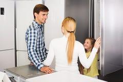 Famille choisissant le réfrigérateur dans le magasin Images libres de droits
