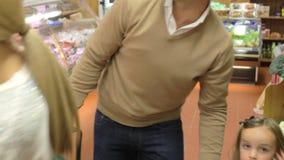 Famille choisissant les légumes frais dans la boutique de ferme banque de vidéos