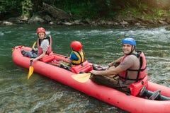 Famille commençant transporter sur par radeau une rivière de montagne photographie stock libre de droits