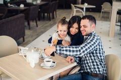 Famille, condition parentale, concept de personnes de technologie - mère heureuse, père et petite fille dînant prenant le selfie  Images stock