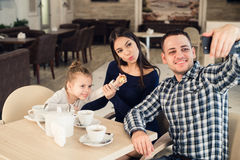 Famille, condition parentale, concept de personnes de technologie - mère heureuse, père et petite fille dînant prenant le selfie  Photographie stock libre de droits