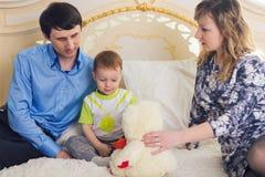 Famille, condition parentale et concept d'enfants - la mère, le père heureux et le fils jouant ainsi que le nounours concernent l Photos stock