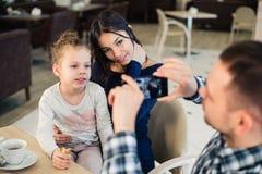 Famille, condition parentale, technologie, concept de personnes - père heureux prenant la photo de sa petites fille et épouse par Image stock