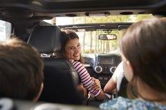 Famille conduisant dans la voiture à couvercle serti sur le voyage par la route de campagne photos stock