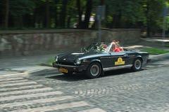 Famille conduisant la voiture à de rétros courses d'automobiles Photos stock