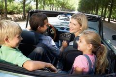Famille conduisant le long dans une voiture de sport Image libre de droits