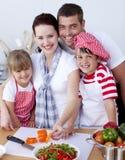 Famille coupant les légumes colorés dans la cuisine Images stock