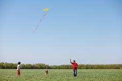 Famille courant avec un cerf-volant Photographie stock