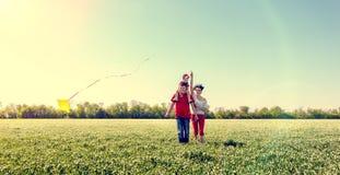 Famille courant avec un cerf-volant Photos libres de droits