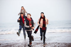 Famille courant le long de la plage d'hiver photos stock