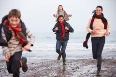 Famille courant le long de la plage d'hiver image stock
