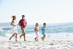Famille courant le long de Sandy Beach image stock