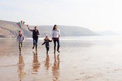 Famille courant le long du cerf-volant de vol de plage d'hiver Images libres de droits